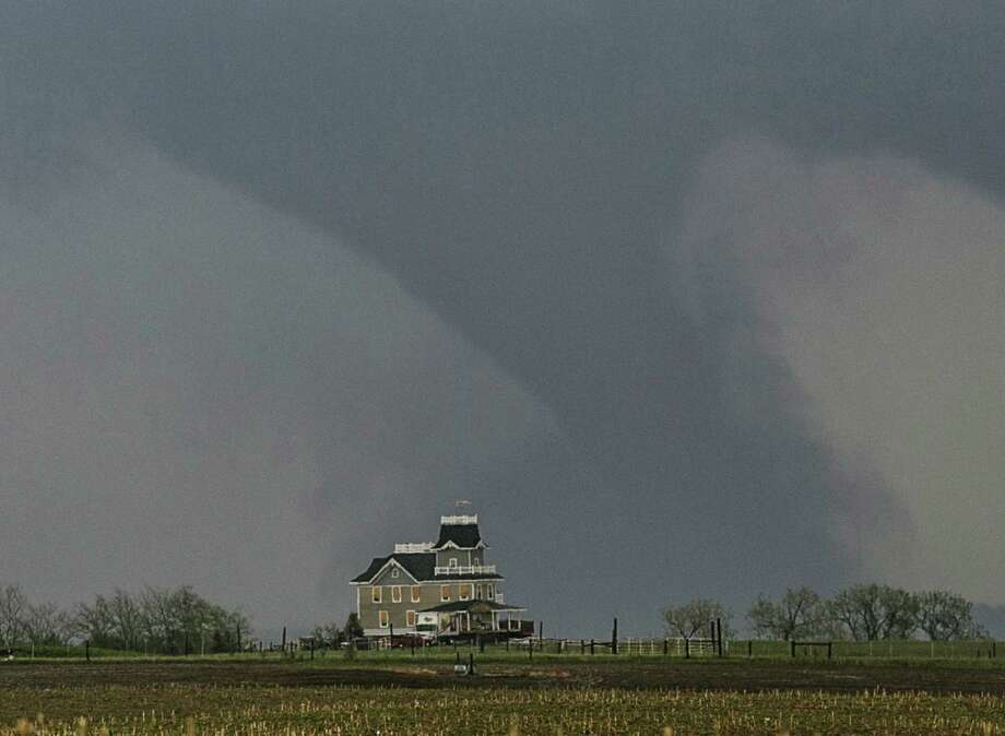 A tornado forms over a house near  Pilger, Neb., Monday, June 16, 2014. At least one person is dead and at least 16 more are in critical condition after two massive tornadoes swept through northeast Nebraska on Monday. Photo: Mark 'Storm' Farnik, AP  / A2014