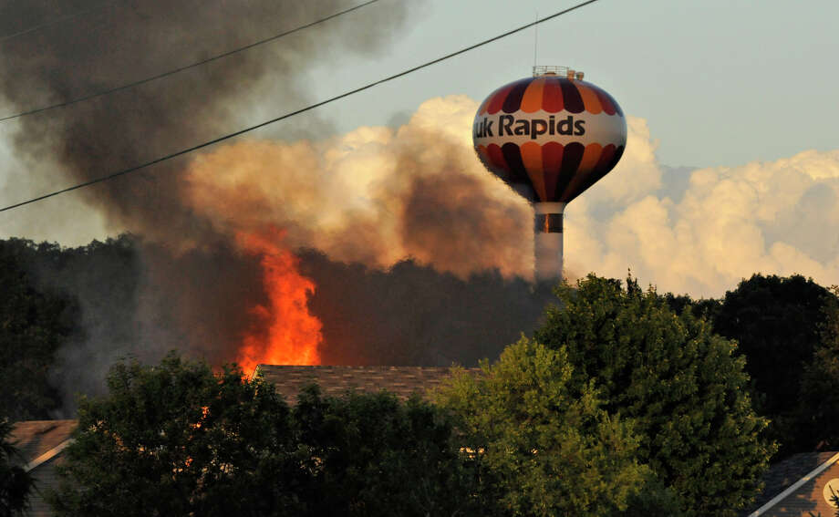 Flames could be seen over the tree tops after a small plane crashed into a home at 731 Garden Place, killing the pilot and passenger and setting the home ablaze,  in Sauk Rapids, Minn., Friday, June 20, 2014. No one else was hurt. Photo: JASON WACHTER, AP  / ST. CLOUD TIMES
