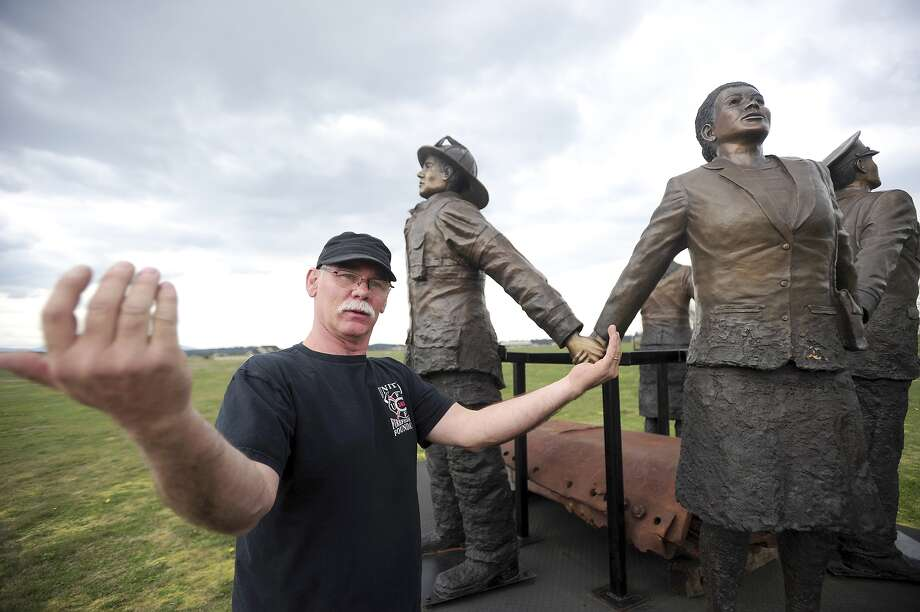 John Jackson explains the significance of the statues in his 9/11 monument holding hands at his home in Tenino, Wash. Jackson, who worked along with the Spirit of America Foundation, built a monument in honor of the people affected by the Sept. 11 terrorist attacks in Pennsylvania, the World Trade Center and the Pentagon. Jackson's original plan was to have the monument, which features a steel girder from one of the World Trade Center towers, placed near the Capitol Campus in Olympia, but his plan was rejected by Washington State Department of Enterprise Services on the basis that it was of national significance, not state significance. Photo: Pete Caster, AP  / The Chronicle