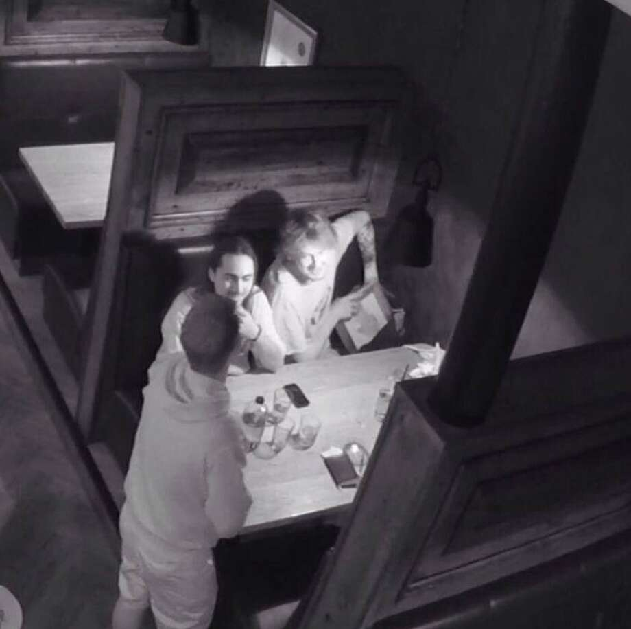 This photo provided by Tyler Christensen,  shows a surveillance photo of a man placing a painting in his backpack at the McMillan Bar and Kitchen in Flagstaff, Ariz.   Two accomplices in the theft of the painting at the restaurant have come forward after a shaming campaign on Facebook. Tyler Christensen, the owner of McMillan Bar and Kitchen, went to social media instead of police after the painting went missing on June 9, 2014.  Christensen posted an open letter and surveillance photo.  He says the two accomplices have since come forward and given $500 to cover the cost of the artwork. Christensen's Facebook post has been shared more than 7,900 times and received more than 4,300 likes and nearly 770 comments. Photo: Uncredited, AP  / AP2014