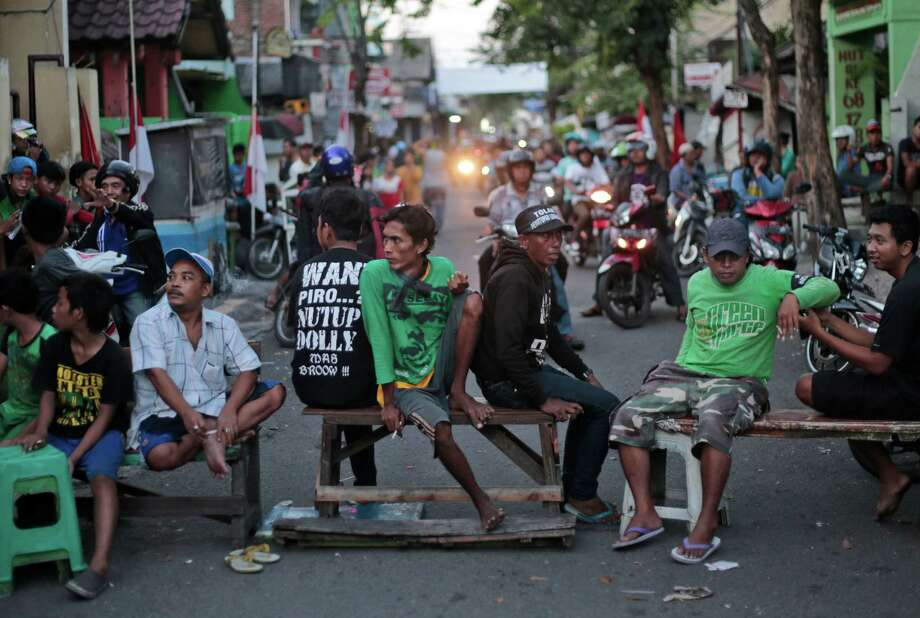 Residents of Dolly red-light district man a road block in protest  against the closing of the prostitution complex in Surabaya, East Java, Indonesia, Wednesday, June 18, 2014. The government has shut down a red-light district in Indonesia's second largest town amid protests by pimps and sex workers as well as dependents. Photo: Dita Alangkara, AP  / AP2014