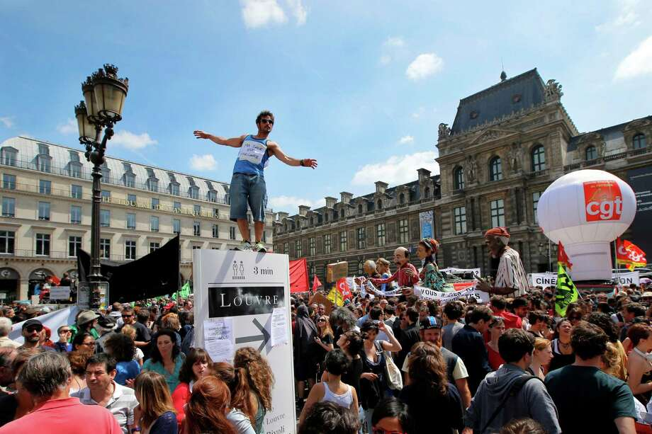 "A man tries to keep his balance on top of a Louvre Museum signboard as he attends a gathering of part-time and temporary arts workers, striking artists and theater personnel, known as ""intermittents"", to protest against government plans to reform the unemployment benefits insurance agreement in Paris, Monday, June 16, 2014. The strike is gathering steam throughout the country, threatening the cancellation of various arts festivals like Avignon Theater festival this summer. Photo: Francois Mori, AP  / AP"