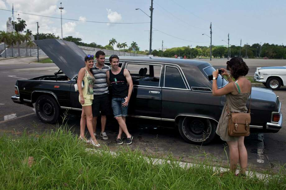 In this June 18, 2014 photo, tourists from Barcelona, Spain take a picture with a Soviet-made limousine taxi cab that once belonged to Fidel Castro's fleet in front of Revolution Plaza in Havana, Cuba. The driver, Moises Suarez, popped the hood so they could get a look at the engine. Photo: Franklin Reyes, AP  / AP2014