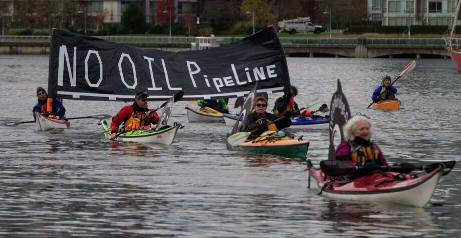 "Kayakers display a ""No Oil Pipeline"" banner during a protest against the Enbridge Northern Gateway pipeline in Vancouver, on Saturday Nov. 16, 2013.  Canada's government on Tuesday, June 17, 2014,  approved a controversial pipeline proposal that would bring oil to the Pacific Coast for shipment to Asia, a major step in the country's efforts to diversify its oil exports if it can overcome fierce opposition from environmental and aboriginal groups. Photo: DARRYL DYCK, AP  / The Canadian Press"