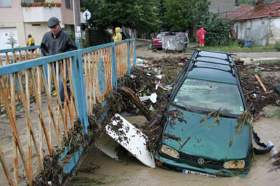 A man walks past debris and cars swept away by severe flooding in the town of Varna, Bulgaria, Friday, June 20, 2014. Bulgarian authorities say ten people have died and several others are missing after heavy rain and flooding hit the Black Sea port city of Varna. Large parts of the Balkan country have been hit by heavy rain and hailstorms, and hundreds of people have been left without electricity and food supplies. Photo: STR, AP  / AP2014