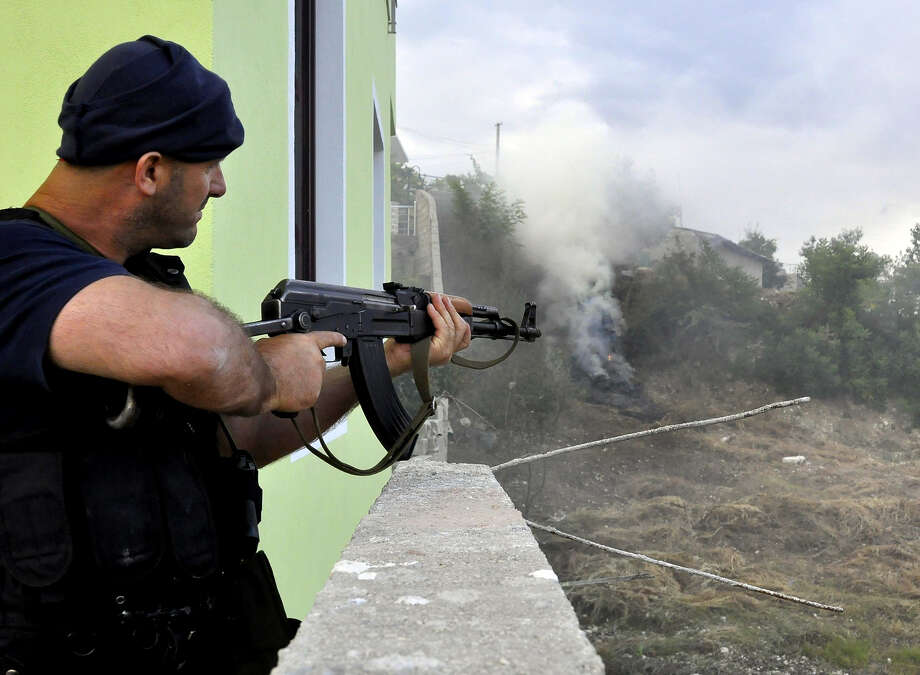 An Albanian police officer fires a gun in the lawless village of Lazarat, 230 kilometers (140 miles) south of capital Tirana, Thursday, June 19, 2014 after battling for five days with well-armed marijuana growers trying to thwart a government crackdown. Some 13 tons of marijuana have been seized and burnt, 80,000 pot plants have been destroyed and a considerable amount of weapons and ammunition found in the houses. Photo: AP  / AP