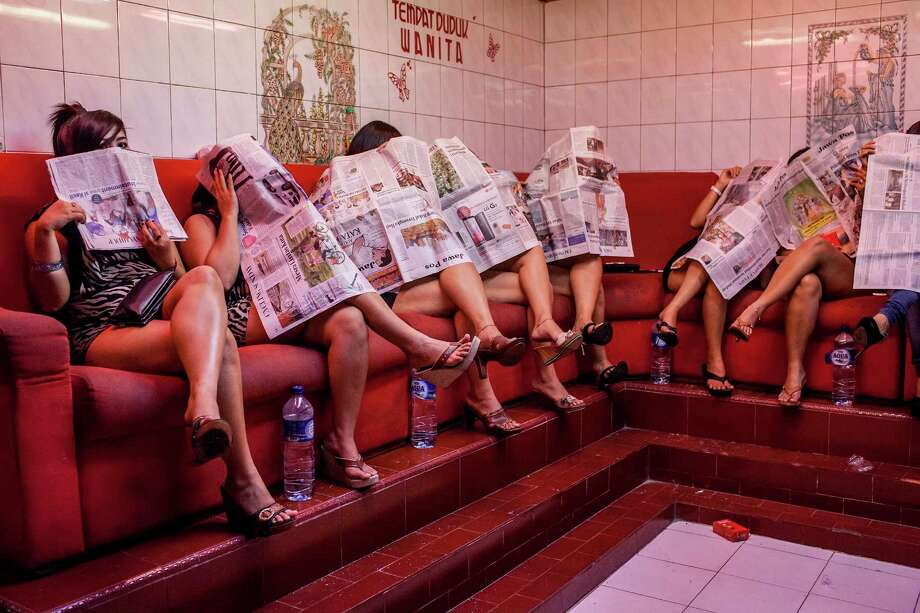 Indonesian commercial female sex workers cover their face as they sit behind the glass inside a brothel as it's activity still runs after being closed by Surabaya's new Mayor at 'Dolly' red-light district on June 19, 2014 in Surabaya, Indonesia. Despite protests by some local residents and sex-workers, Surabaya's new Mayor, Tri Rismaharini closed the 'Dolly' and neighbouring 'Jarak' red-light district in Surabaya, Indonesia's second-largest city, on Wednesday. Many of the community support the end of sex trade in Dolly's streets, with some Islamic groups reportedly threatening violence should the brothels not remain closed. Photo: Ulet Ifansasti, Getty Images / 2014 Getty Images