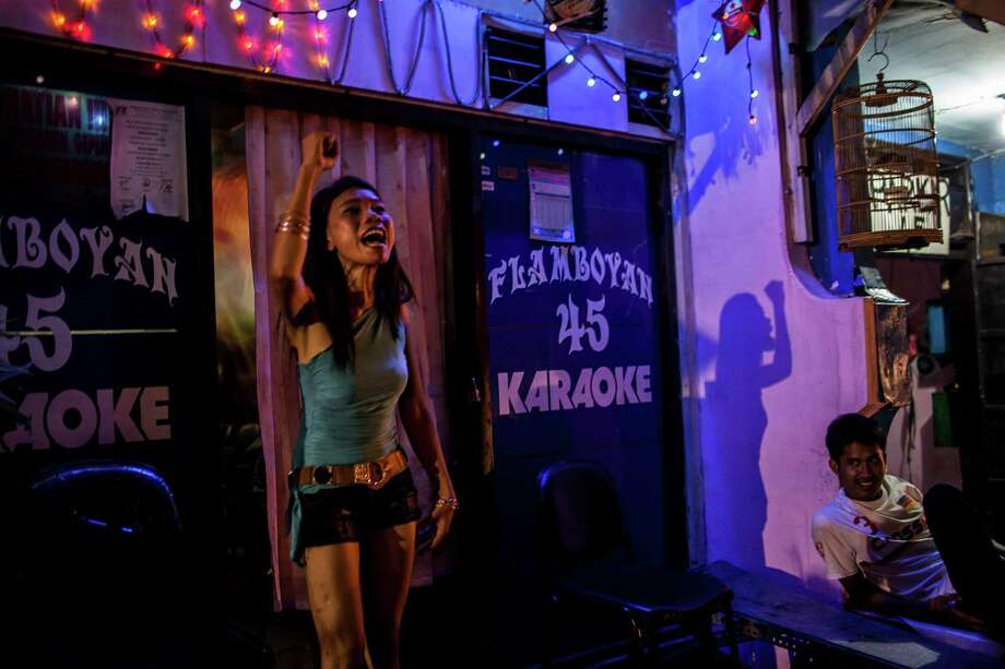 An Indonesian commercial female sex worker shouts against closure in front of a brothel as it still runs after being closed by Surabaya's Mayor at 'Jakak' red-light district on June 19, 2014 in Surabaya, Indonesia. Despite protests by some local residents and sex-workers, Surabaya's new Mayor, Tri Rismaharini closed the 'Dolly' and neighbouring 'Jarak' red-light district in Surabaya, Indonesia's second-largest city, on Wednesday. Many of the community support the end of sex trade in Dolly's streets, with some Islamic groups reportedly threatening violence should the brothels not remain closed. Photo: Ulet Ifansasti, Getty Images / 2014 Getty Images
