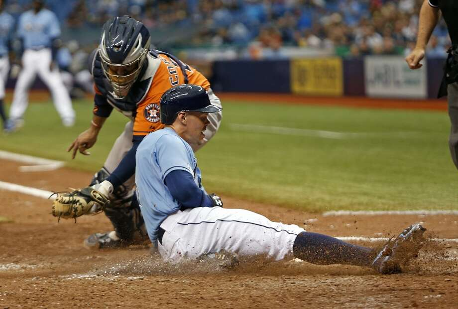 June 22: Rays 5, Astros 2  Brandon Guyer slides safely home in front of catcher Carlos Corporan to score off of a sacrifice fly by Sean Rodriguez during the eighth inning. Photo: Brian Blanco, Getty Images