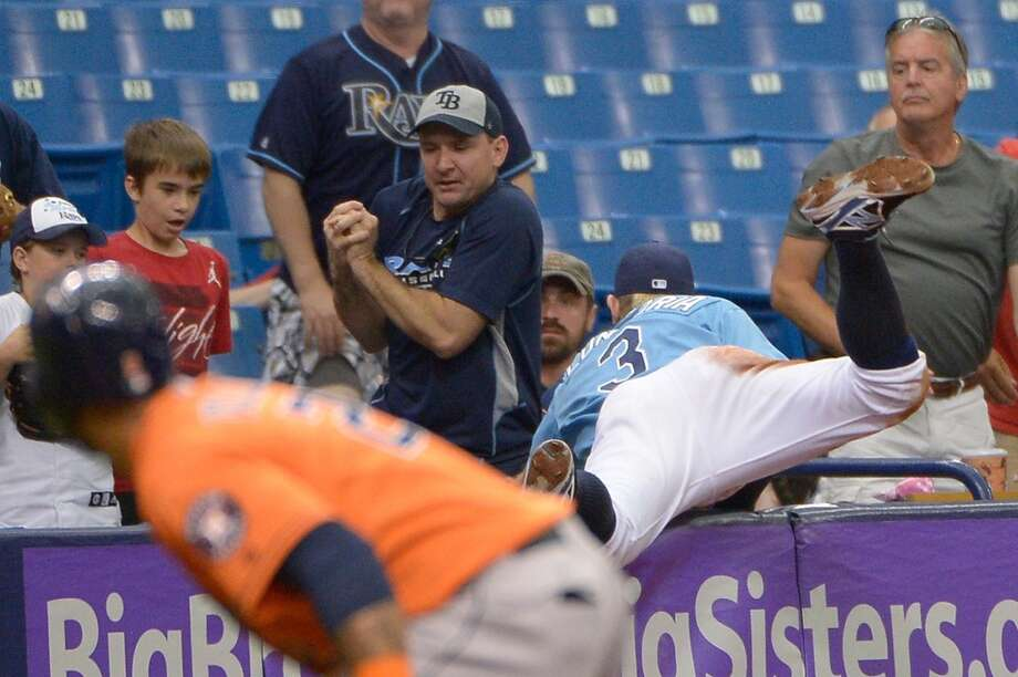 A fan catches a foul ball hit by Astros' Jose Altuve as Rays third baseman Evan Longoria dives into the stands for the ball during the third inning. Photo: Phelan M. Ebenhack, Associated Press
