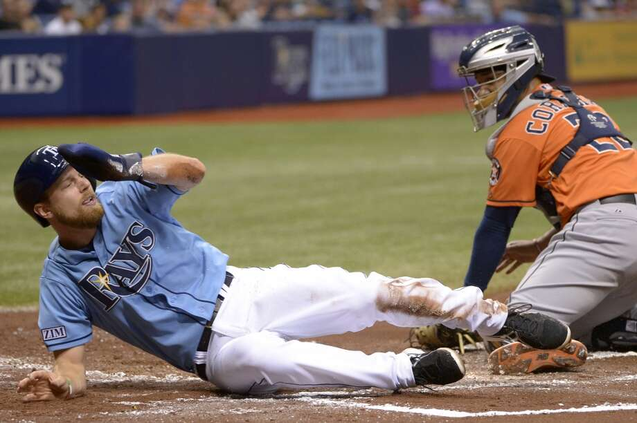 The Rays' Ben Zobrist, left, scores past Astros catcher Carlos Corporan on a single hit by Evan Longoria during the first inning. Photo: Phelan M. Ebenhack, Associated Press