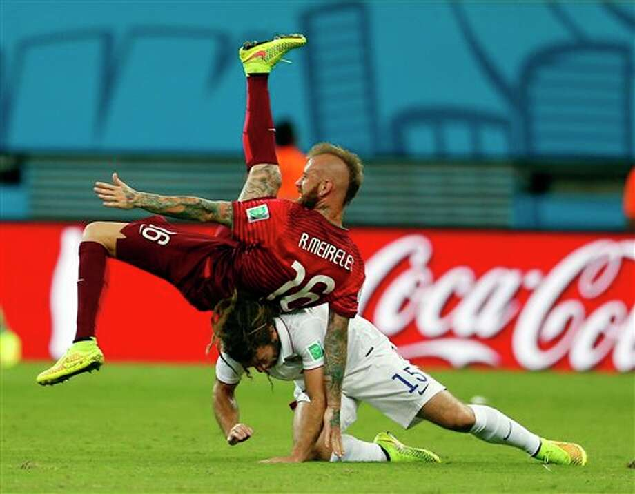 Portugal's Raul Meireles falls on top of United States' Kyle Beckerman during the group G World Cup soccer match between the United States and Portugal at the Arena da  Amazonia in Manaus, Brazil, Sunday, June 22, 2014. (AP Photo/Julio  Cortez