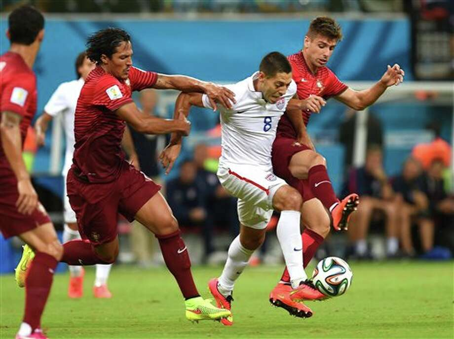 United States' Clint Dempsey,  centre, is challenged by Portugal's Bruno Alves, left, and Portugal's  Miguel Veloso, right, during the group G World Cup soccer match between the USA and Portugal at the Arena da Amazonia in  Manaus, Brazil, Sunday, June 22, 2014. (AP Photo/Paulo Duarte)