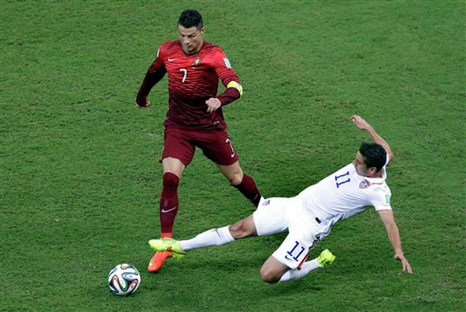 Portugal's Cristiano Ronaldo, left, is challenged by United States' Alejandro Bedoya during the group G World Cup soccer match between the USA and Portugal at the Arena da Amazonia in  Manaus, Brazil, Sunday, June 22, 2014. (AP Photo/Themba Hadebe)