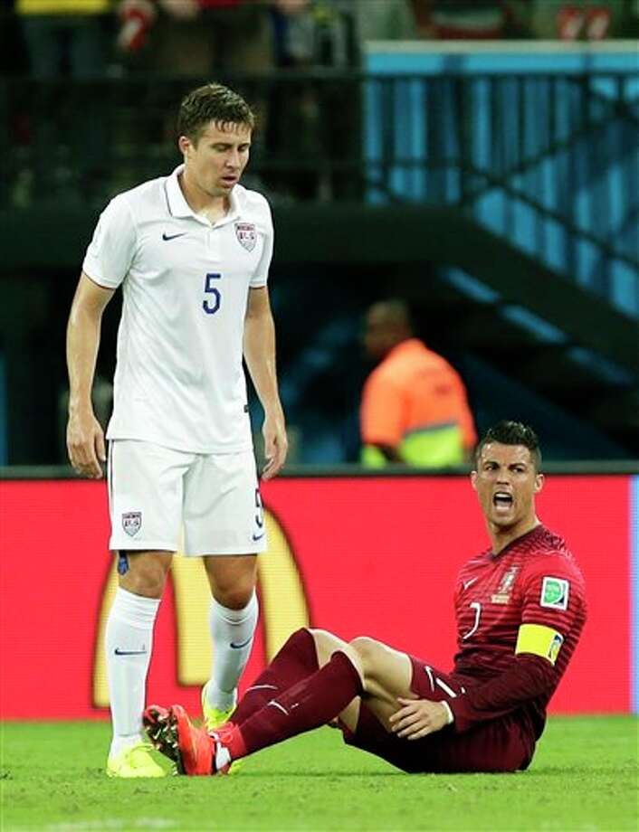 Portugal's Cristiano Ronaldo, right, yells as he sits on the pitch next to United States' Matt Besler during the group G WorldCup soccer match between the United States and Portugal at the Arena da  Amazonia in Manaus, Brazil, Sunday, June 22, 2014. (AP Photo/Marcio Jose  Sanchez)