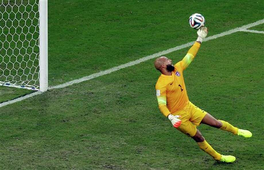 United States' goalkeeper Tim Howard tips a ball to deflect it over the goal during the group G World Cup soccer match between the USA and Portugal at the Arena da Amazonia in  Manaus, Brazil, Sunday, June 22, 2014. (AP Photo/Themba Hadebe)