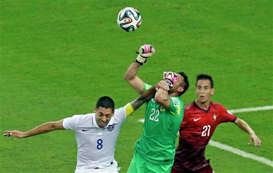 Portugal's goalkeeper Beto,  center, clears a ball ahead of United States' Clint Dempsey, left, and  Portugal's Joao Pereira, right, during the group G World Cup soccer match between the USA and Portugal at the Arena da Amazonia in  Manaus, Brazil, Sunday, June 22, 2014. (AP Photo/Themba Hadebe)