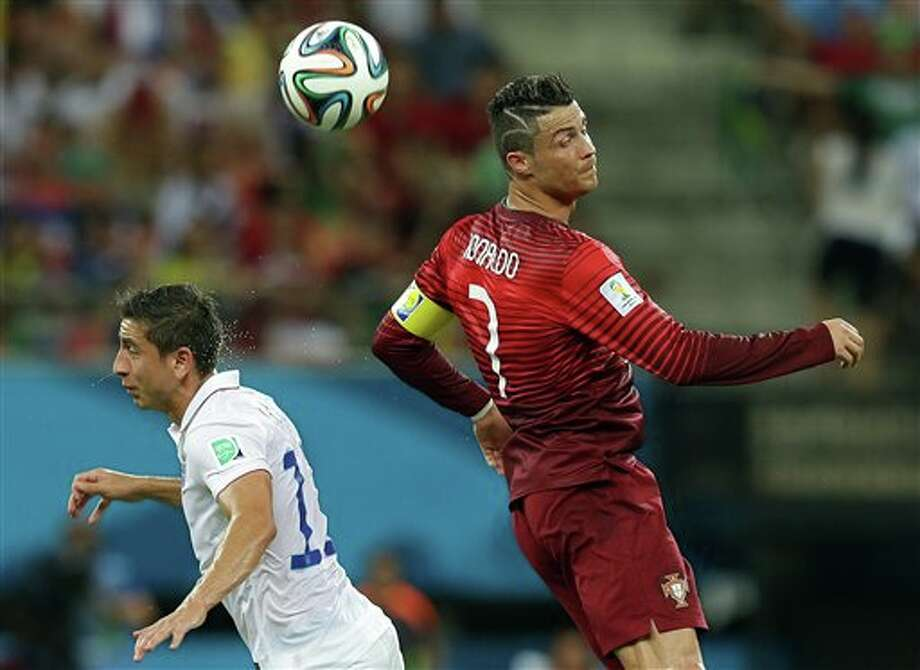 Portugal's Cristiano Ronaldo heads the ball over United States' Alejandro Bedoya during the group G WorldCup soccer match between the USA and Portugal at the Arena da Amazonia in  Manaus, Brazil, Sunday, June 22, 2014. (AP Photo/Martin Mejia)
