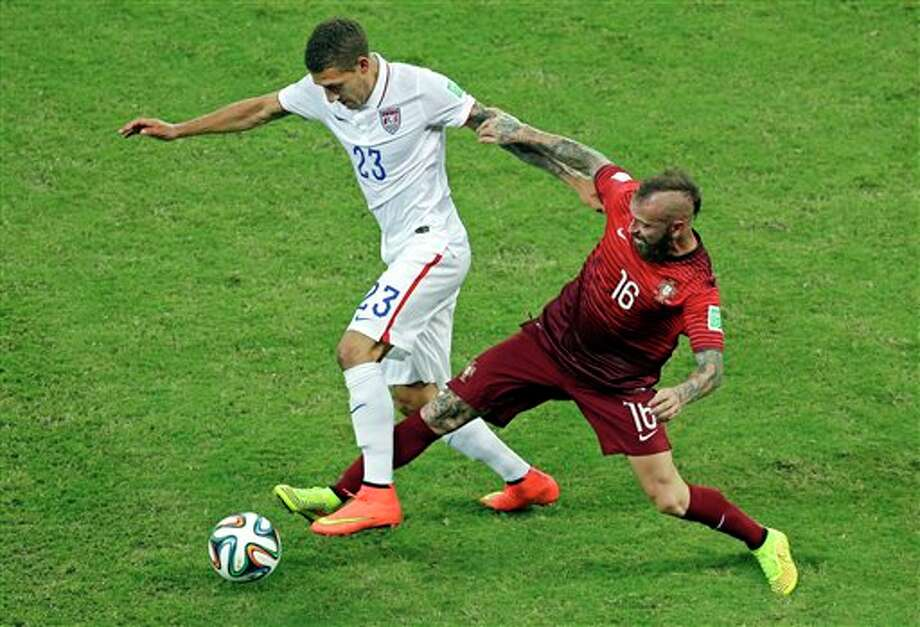 United States' Fabian Johnson, left, is challenged by Portugal's Raul Meireles during the group G WorldCup soccer match between the USA and Portugal at the Arena da Amazonia in  Manaus, Brazil, Sunday, June 22, 2014. (AP Photo/Themba Hadebe)