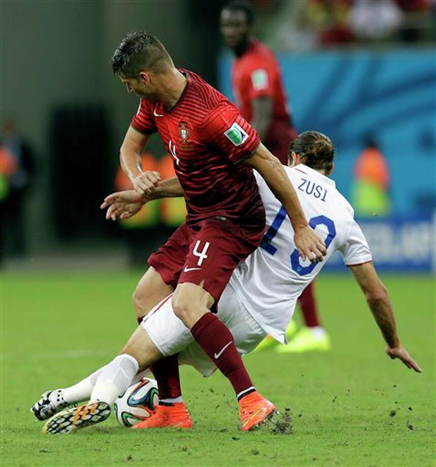 ortugal's Miguel Veloso gets tangled with United States' Graham Zusi during the group G World Cup soccer match between the USA and Portugal at the Arena da Amazonia in  Manaus, Brazil, Sunday, June 22, 2014. (AP Photo/Martin Mejia)