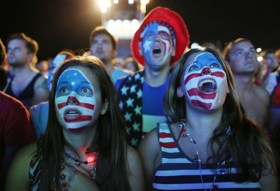 Fans with their faces painted with the U.S. national soccer team's colors, watch a live telecast of the group G World Cup match between United States and Portugal, inside the FIFA Fan Fest area on Copacabana beach, in Rio de Janeiro, Brazil, Sunday, June 22, 2014. (AP Photo/Leo Correa) Photo: Leo Correa, Associated Press