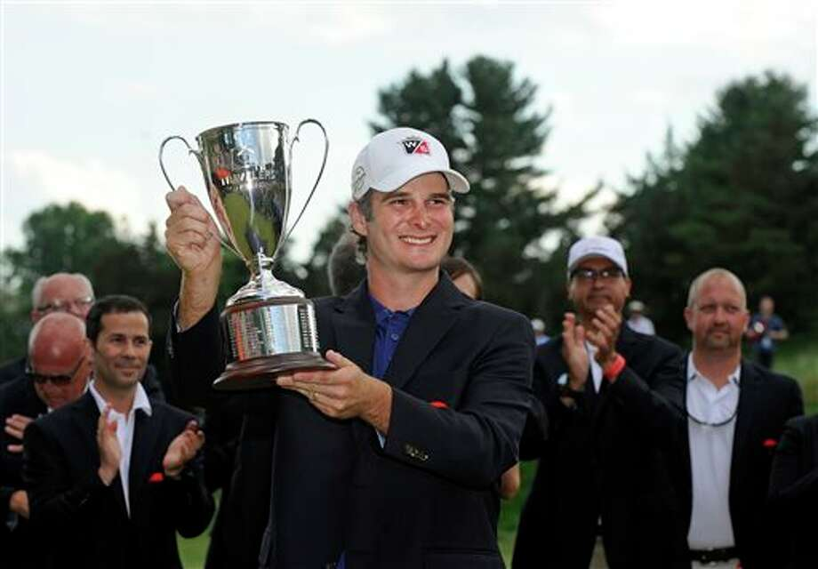 Kevin Streelman holds the trophy after winning the Travelers Championship golf tournament in Cromwell, Conn., Sunday, June 22, 2014. Streelman  finished his round with seven straight birdies to win the tournament at  15-under par. (AP Photo/Fred Beckham)