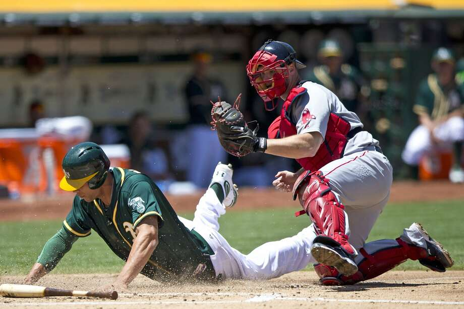 Kyle Blanks was tagged out by Boston catcher David Ross when he tried to score on Stephen Vogt's grounder. Photo: Jason O. Watson, Getty Images