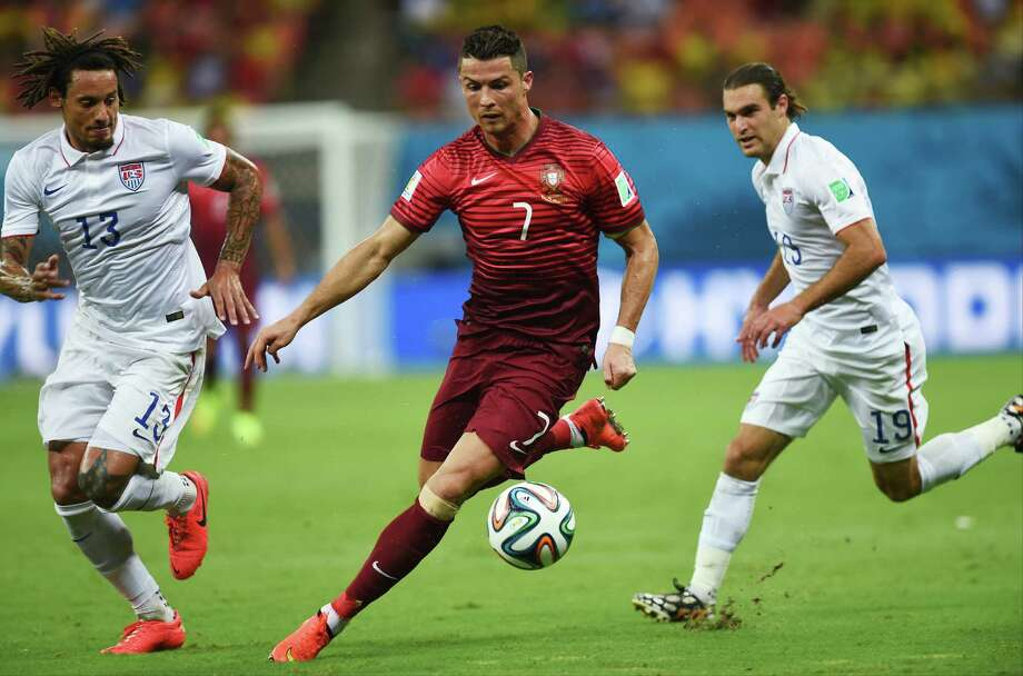 Portugal's Cristiano Ronaldo, center, runs with the ball between United States' Jermaine Jones, left, and United States' Graham Zusi, right, during the group G World Cup soccer match between the USA and Portugal at the Arena da Amazonia in Manaus, Brazil, Sunday, June 22, 2014. (AP Photo/Paulo Duarte) Photo: Paulo Duarte, Associated Press / AP