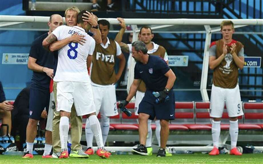 United States' head coach Juergen Klinsmann huts United States' Clint Dempsey as Dempsey is substituted during the group G World Cup soccer match between the USA and Portugal at the Arena da Amazonia in  Manaus, Brazil, Sunday, June 22, 2014. (AP Photo/Paulo Duarte)