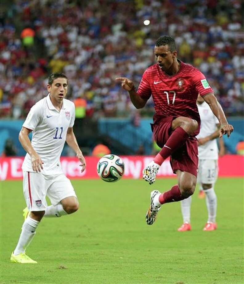 Portugal's Nani, right, controls the ball as United States' Alejandro Bedoya looks on at left, during the group G WorldCup soccer match between the United States and Portugal at the Arena da  Amazonia in Manaus, Brazil, Sunday, June 22, 2014. (AP Photo/Marcio Jose  Sanchez)