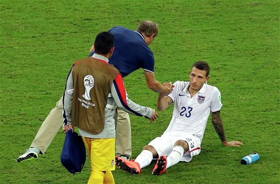 United States' Fabian Johnson, right, shakes hand with head coach Juergen Klinsmann after a 2-2 draw in the group G WorldCup soccer match between the USA and Portugal at the Arena da Amazonia in  Manaus, Brazil, Sunday, June 22, 2014. (AP Photo/Themba Hadebe)