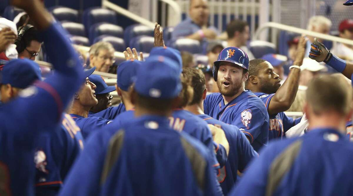 New York Mets batter Daniel Murphy (facing camera) celebrates in the dugout after hitting a three-run home run during the fourth inning of a baseball game in Miami against the Miami Marlins, Sunday, June 22, 2014. The Mets won 11-5. (AP Photo/J Pat Carter) ORG XMIT: FLJC124