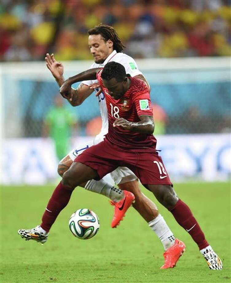 United States' Jermaine Jones, rear, and Portugal's Silvestre Varela battle for the ball during the group G WorldCup soccer match between the USA and Portugal at the Arena da Amazonia in  Manaus, Brazil, Sunday, June 22, 2014. (AP Photo/Paulo Duarte)