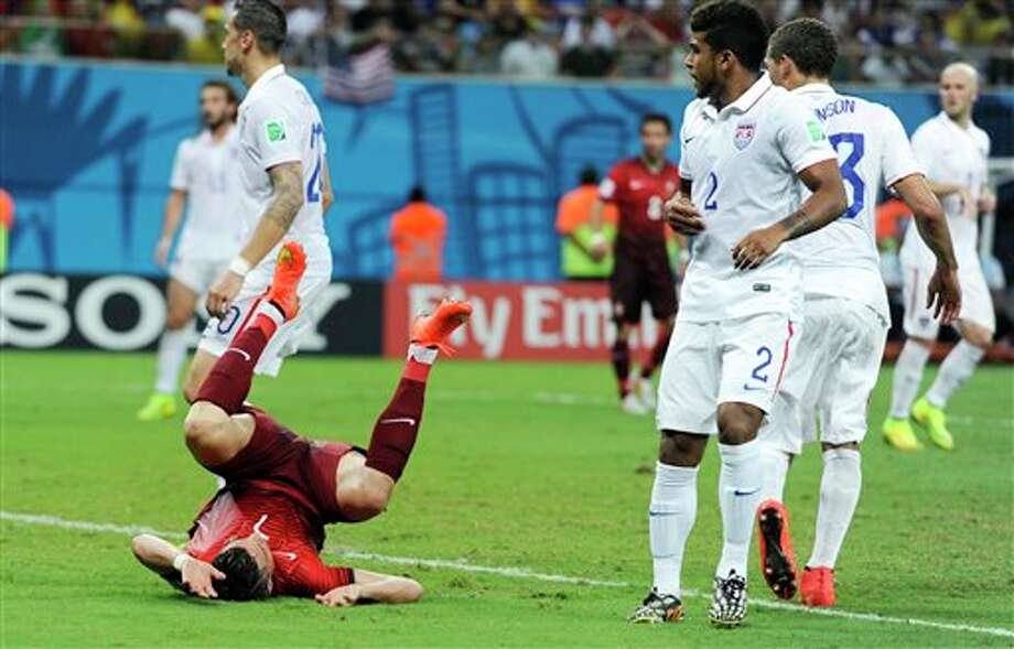 Portugal's Cristiano Ronald, lower left, takes a tumble during the group G WorldCup soccer match between the USA and Portugal at the Arena da Amazonia in  Manaus, Brazil, Sunday, June 22, 2014. (AP Photo/Paulo Duarte)