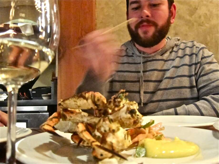 Adam Dorris attacks a hearth roasted Dungeness crab at Camino in Oakland, an inspiration for Pax Americana. Photo: Alison Cook