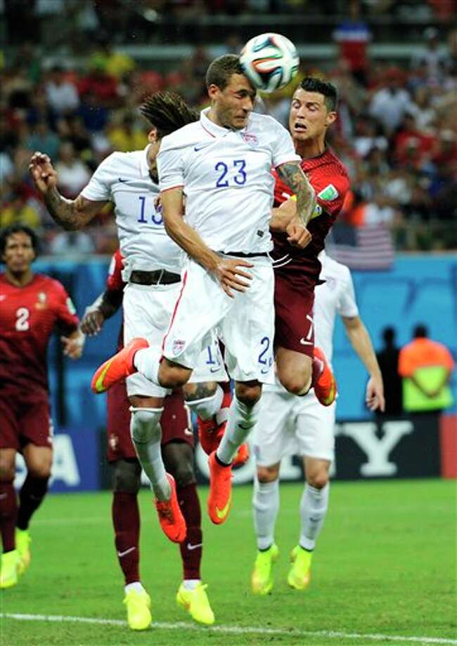 United States' Fabian Johnson (23) heads the ball away from Portugal's Cristiano Ronaldo, right, during the group G WorldCup soccer match between the USA and Portugal at the Arena da Amazonia in  Manaus, Brazil, Sunday, June 22, 2014. (AP Photo/Paulo Duarte)