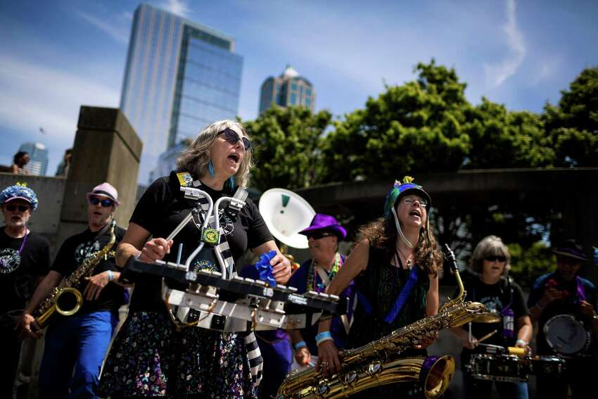 Toting a variety of instruments, members Artesian Rumble Arkestra perform for a crowd at the seventh annual HONK! Fest West in Seattle?•s Waterfront Park in Seattle, Wash. HONK! Fest's mission is to celebrate community music in public spaces with fanfare performances representing diverse musical influences. The festival ran from Friday through Sunday.