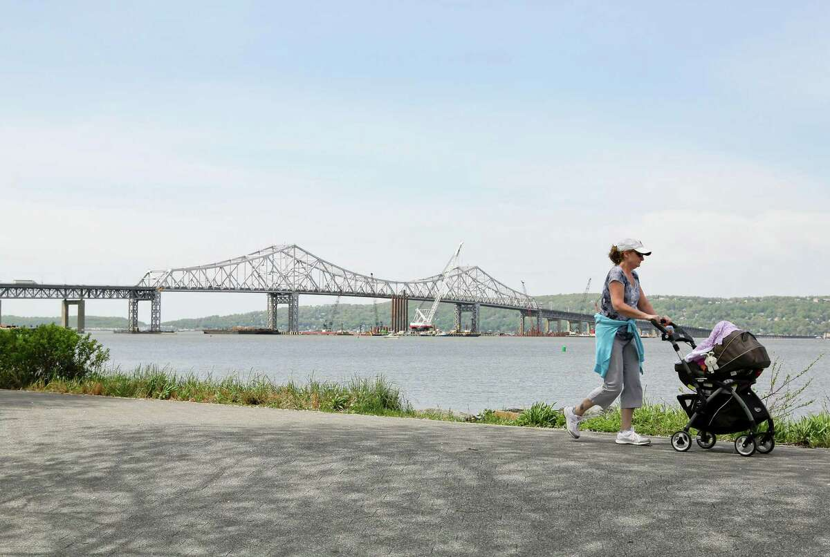 A woman takes a stroll with her child along the Westchester Riverwalk just north of the Tappan Zee Bridge, Tuesday, May 13, 2014, in Tarrytown, N.Y. On Wednesday, President Barack Obama plans to speak by the bridge just north of New York City to press his case that a key federal government fund used to pay for the nation's roads, bridges and ports is running dry and that the economy would be damaged if it is not replenished. (AP Photo/Julie Jacobson) ORG XMIT: NYJJ104