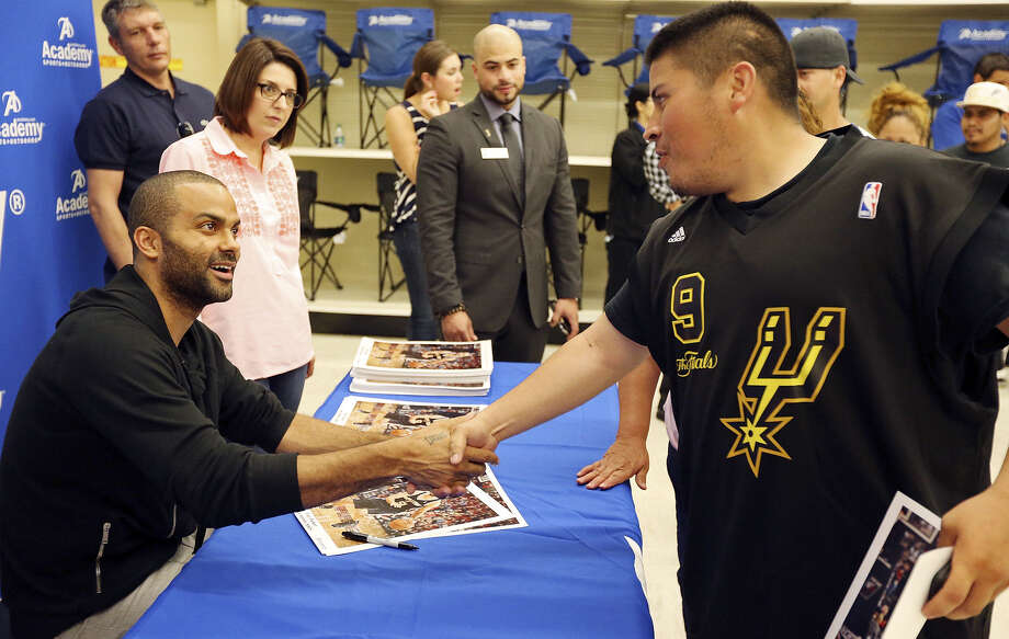 Spurs point guard Tony Parker shakes hands with one of his many fans, Eligardo Rodriguez. Photo: Edward A. Ornelas / San Antonio Express-News / © 2014 San Antonio Express-News