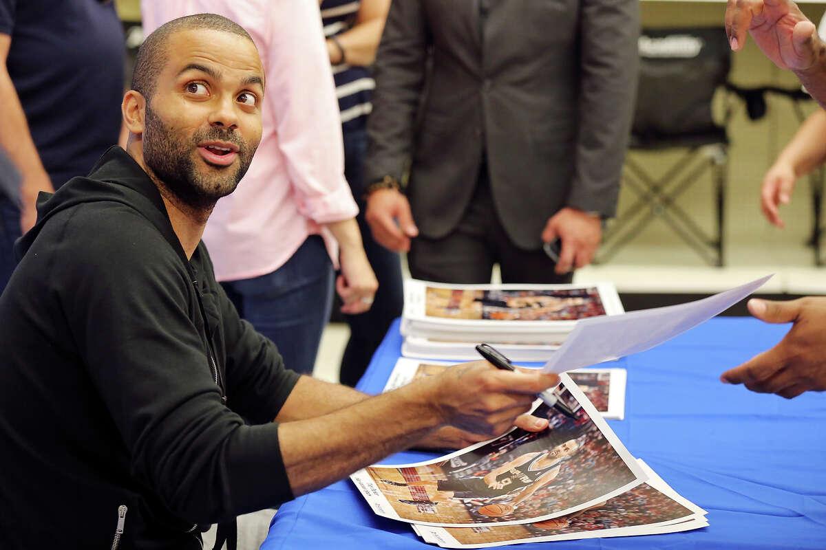 San Antonio Spurs' Tony Parker signs autographs for fans Sunday June 22, 2014 at Academy.