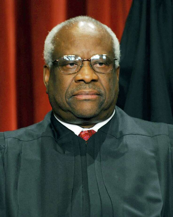 (FILES) US Supreme Court Associate Justice Clarence Thomas participates in the courts official photo session on October 8, 2010 at the Supreme Court in Washington, DC. Thomas' wife Virginia left a voicemail message on Anita Hill's office phone over the weekend, asking her to apologize for the allegations that surfaced at Thomas' confirmation hearings for a seat on the high court bench in 1991. Hill, who is a professsor at Brandeis University called the message inappropriate and says she has no intention of apologizing for her testimony. AFP PHOTO / TIM SLOAN (Photo credit should read TIM SLOAN/AFP/Getty Images) Photo: TIM SLOAN / AFP