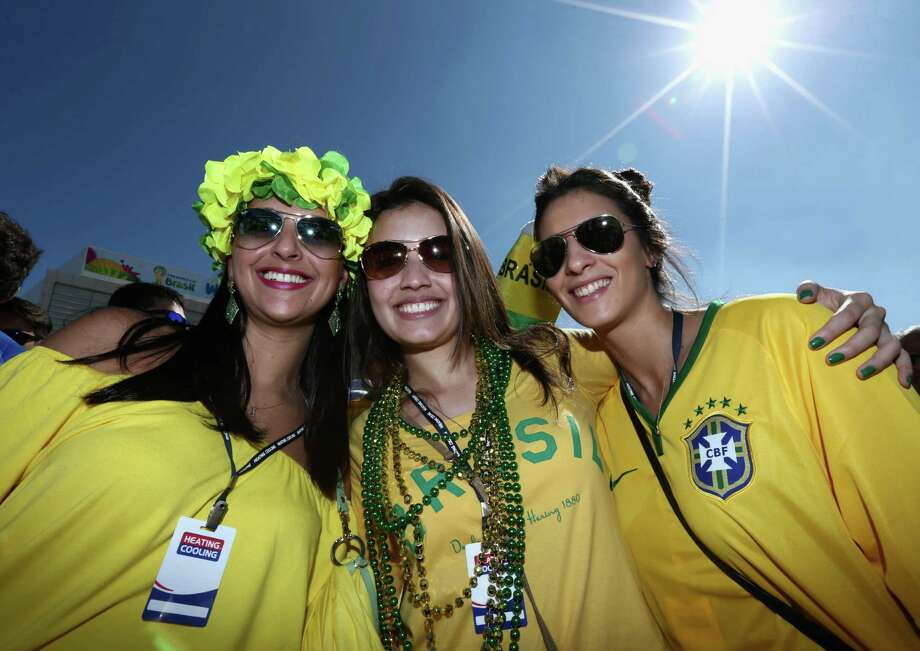 SAO PAULO, BRAZIL - JUNE 12:  Fans of Brazil pose before the Opening Ceremony of the 2014 FIFA World Cup Brazil prior to the Group A match between Brazil and Croatia at Arena de Sao Paulo on June 12, 2014 in Sao Paulo, Brazil. Photo: Warren Little, Getty Images / 2014 Getty Images