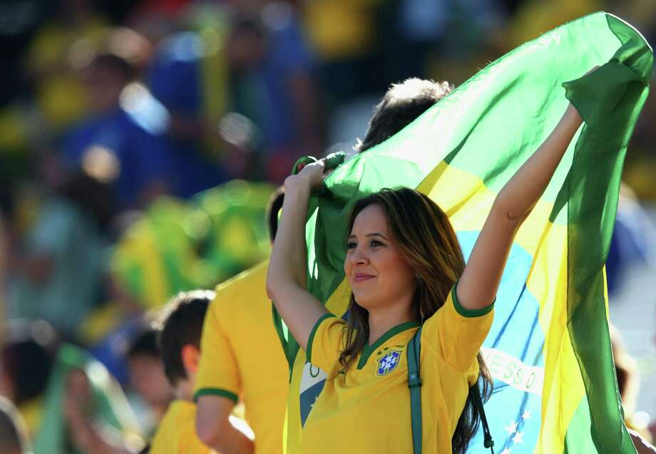 SAO PAULO, BRAZIL - JUNE 12: A Brazil fan waves the Brazilian flag before the Opening Ceremony of the 2014 FIFA World Cup Brazil prior to the Group A match between Brazil and Croatia at Arena de Sao Paulo on June 12, 2014 in Sao Paulo, Brazil. Photo: Adam Pretty, Getty Images / 2014 Getty Images
