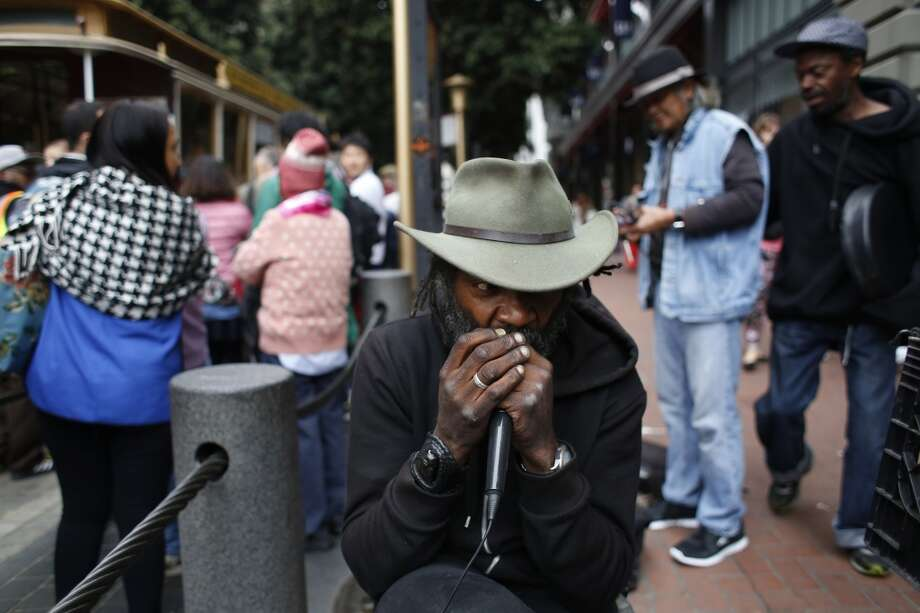 "Delta blues harmonica player Vincente ""Blue"" Blupriest plays to an audience lined up for an uphill ride at the Powell Street cable car turnaround in San Francisco, Calif. When he first started playing their in the late 1990s to a captive audience his performance was frowned upon but now he and the others who take turns playing their have become accepted part of the territory. Photo: Mike Kepka , The Chronicle"