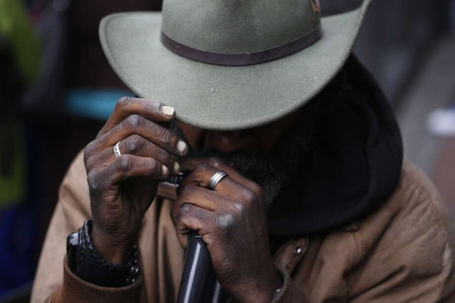 "Delta blues harmonica player Vincente ""Blue"" Blupriest  gives his signature hat tip after someone added to his tip jar during a song at the Powell Street cable car turnaround in San Francisco, Calif. Photo: Mike Kepka, The Chronicle"