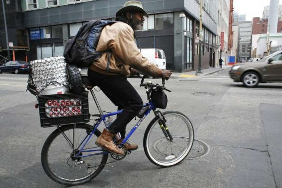 "With eleven dollars in his pocket from his morning performance at the cable car turnaround, delta blues harmonica player Vincente ""Blue"" Bluepriest rides away on his bike in San Francisco, Calif. Photo: Mike Kepka, The Chronicle"