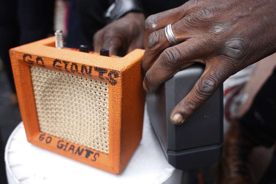 "Delta blues harmonica player Vincente ""Blue"" Blupriest checks the battery power on his miniature amp before playing at the Powell Street cable car turnaround in San Francisco, Calif. Photo: Mike Kepka, The Chronicle"