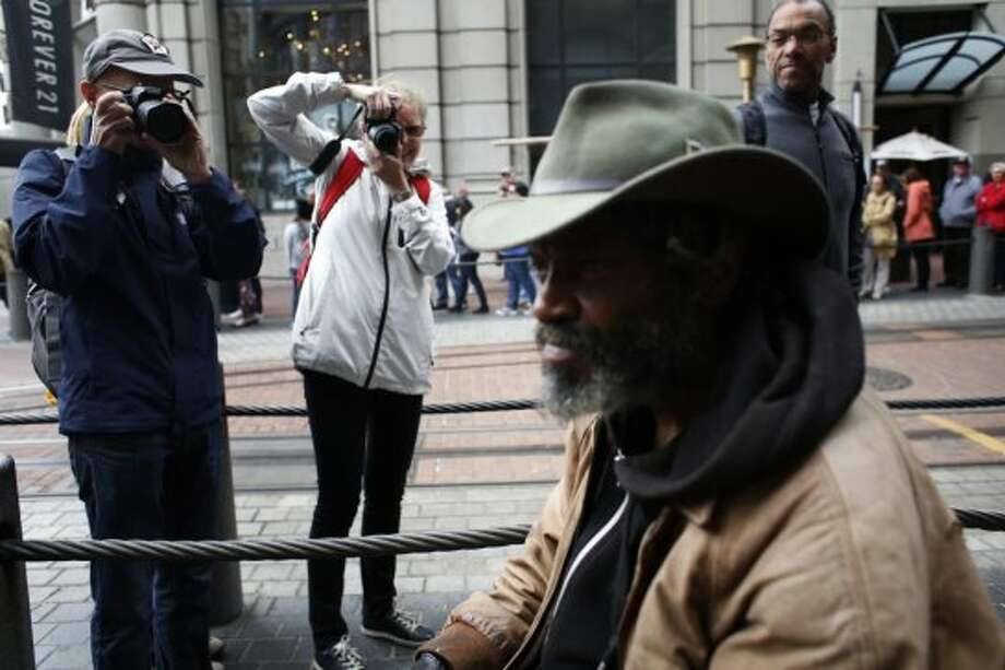 "Delta blues harmonica player Vincente ""Blue"" Blupriest is barraged by the lenses of tourists lined up for an uphill ride at the Powell Street cable car turnaround in San Francisco, Calif. Photo: Mike Kepka, The Chronicle"