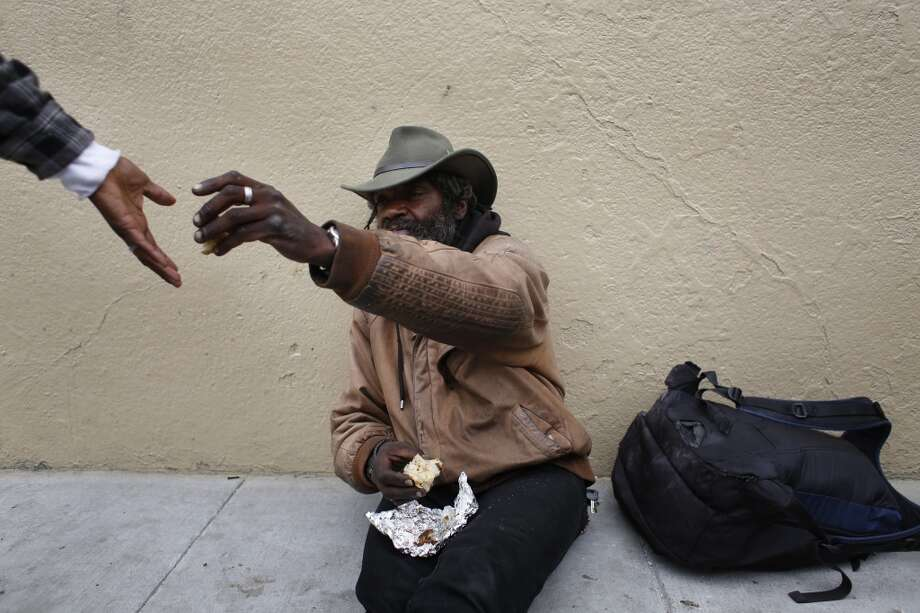 "Delta blues harmonica player Vincente ""Blue"" Blupriest shares a part of a breakfast muffin he purchased with his meager proceeds his morning set at the Powell Street cable car turnaround in San Francisco, Calif. Photo: Mike Kepka, The Chronicle"
