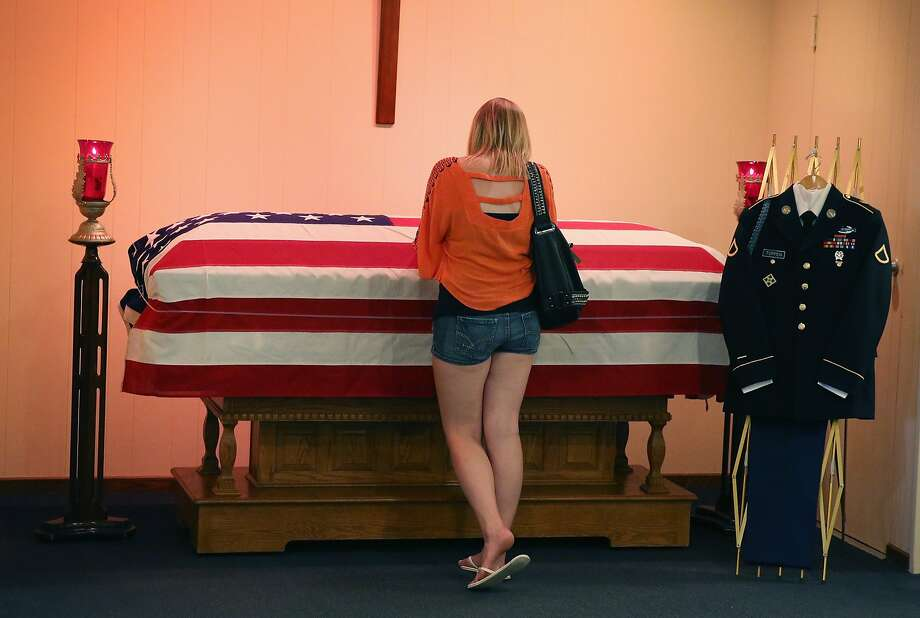 MOKENA, IL - JUNE 22:  Jackie Rozek spends a quiet moment with the remains of her long-time boyfriend, U.S. Army Pfc. Aaron Toppen in a chapel at Vandenberg Funeral Home on June 22, 2014 in Mokena, Illinois. Toppen, 19, was killed alongside four other American soldiers and an Afghan soldier in a friendly fire airstrike during a firefight earlier this month in Afghanistan. Toppen will be buried on Tuesday in his hometown of Mokena, Illinois.  (Photo by Scott Olson/Getty Images) Photo: Scott Olson, Getty Images